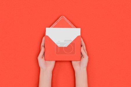 Photo pour Vue de dessus partielle de la personne qui détient l'enveloppe rouge avec carte blanche vierge isolé sur le rouge - image libre de droit