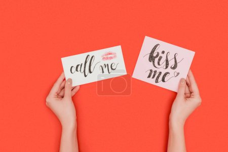 partial top view of person holding cards with kiss me and call me inscriptions and kiss mark isolated on red