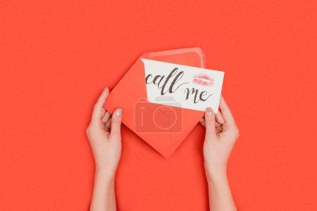 Photo pour Recadrée tir de personne qui détient l'enveloppe rouge et carte avec kiss marque et appelez-moi inscription isolée sur rouge - image libre de droit