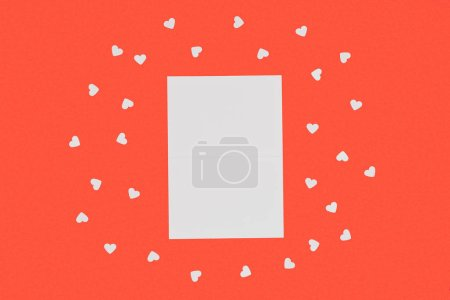 top view of blank white card and small hearts isolated on red