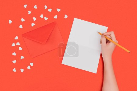 cropped shot of person writing in white card, red envelope and small hearts isolated on red