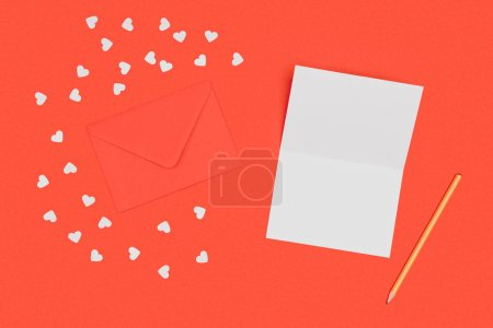 top view of blank white card, pencil, red envelope and small hearts isolated on red