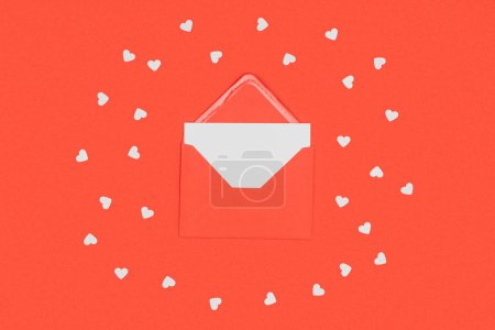close-up view of red envelope with white card and small hearts isolated on red