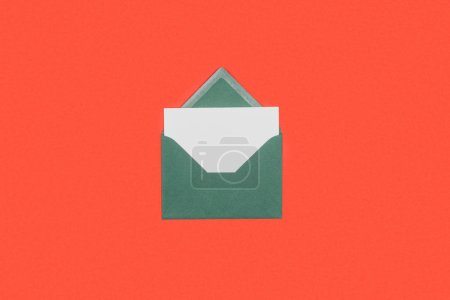 close-up view of green envelope with white card isolated on red