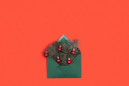 close-up view of green envelope with fir twigs and shiny christmas baubles isolated on red