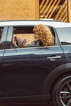side view of curly redhead woman leaning out from car and taking selfie on smartphone