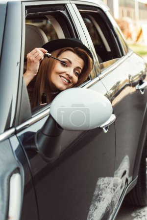happy adult woman in black hat looking at wing mirror while doing make up in car