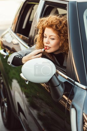 selective focus of curly ginger woman looking at wing mirror while using red lipstick in car