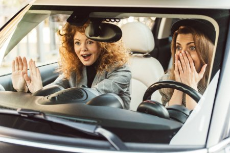 Photo for Surprised adult female friends gesturing by hands and sitting in car - Royalty Free Image