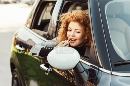 happy ginger woman looking at wing mirror while using red lipstick in car