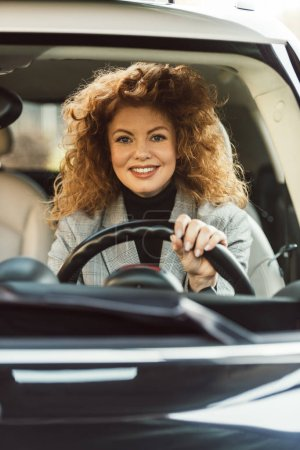 smiling attractive curly redhead woman driving car