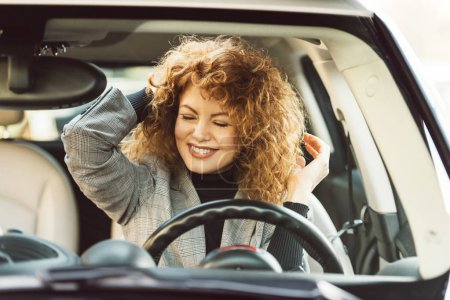 Photo for Happy beautiful curly ginger woman with closed eyes sitting in car - Royalty Free Image