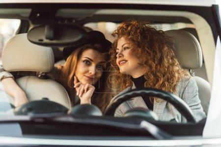 Foto de Sonriente mujer de jengibre hablando con la amiga mientras ella sentada en el asiento trasero del coche - Imagen libre de derechos