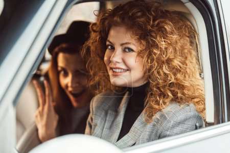 portrait of cheerful ginger woman looking at camera while her female friend showing victory sign in car