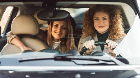 lockige Ingwerfrau Auto fährt, während ihre lächelnde Freundin auf dem Rücksitz sitzt