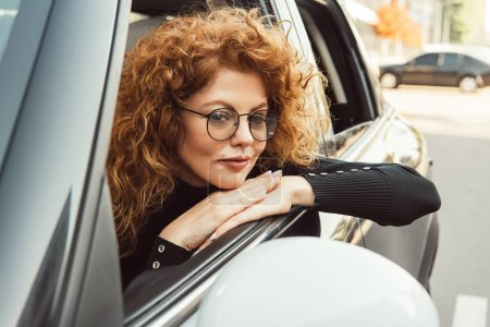 selective focus of redhead ginger woman in eyeglasses looking at wing mirror in car