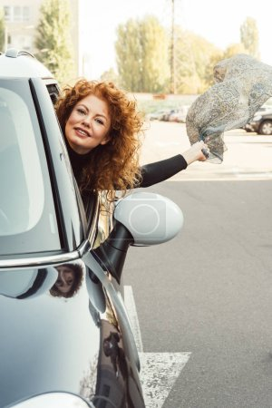 happy curly ginger woman leaning out from car and holding shawl at urban street