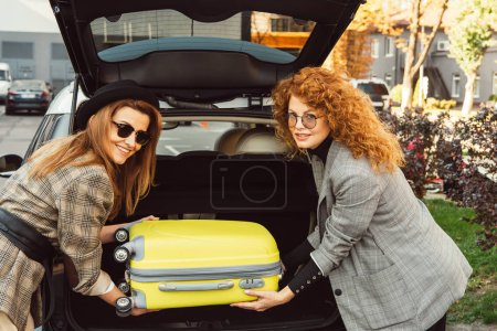 Photo for Beautiful stylish female tourists in sunglasses and jackets putting wheeled bag into car trunk at city street - Royalty Free Image