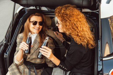 Photo for Smiling adult women in jackets clinking by soda bottles in car trunk at urban street - Royalty Free Image