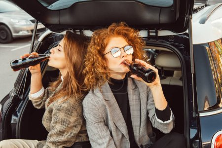 Photo for High angle view of female friends in jackets drinking soda in car trunk at urban street - Royalty Free Image