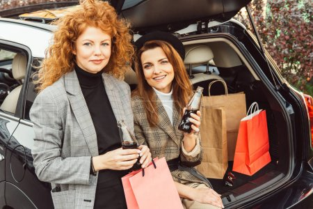 happy female friends with soda bottles and shopping bags looking at camera near car at city street