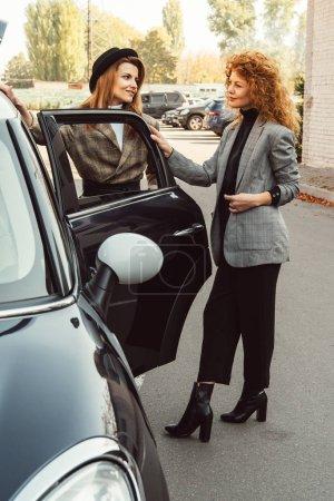 stylish female friends in jackets talking near car at urban street
