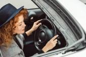 """Постер, картина, фотообои """"высокий угол зрения модной женщина в черной шляпе и Серый жакет, сидя на рулевое колесо в автомобиле"""""""
