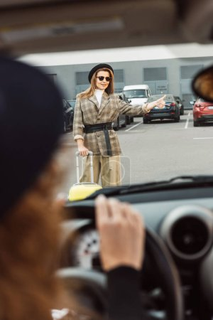 Photo for Partial view of woman sitting at steering wheel while stylish female tourist doing thumb up gesture near wheeled bag at urban street - Royalty Free Image