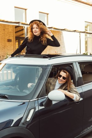 Photo for Attractive curly ginger woman leaning out from car hatchway while her female friend driving car at city street - Royalty Free Image