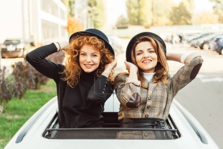 portrait of happy female friends in black hats leaning out from car hatchway at urban street