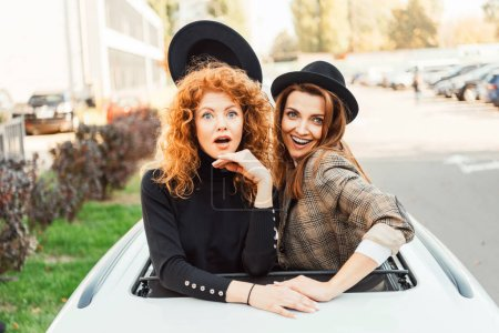 cheerful woman taking off black hat from her shocked female friend while they leaning out from car hatchway at city street
