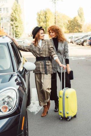 Photo pour Élégants touristes femmes en manteaux et chapeaux noirs debout avec roues sac près de voiture à la rue de la ville - image libre de droit