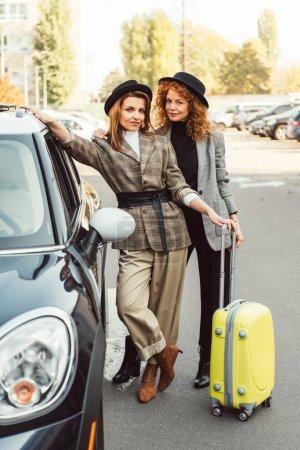 Photo pour Touristes féminins à la mode en manteaux et chapeaux noirs debout avec roues sac près de voiture à la rue de la ville - image libre de droit