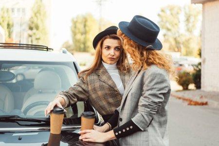 Foto de Amigas de moda en sombreros negros y chaquetas con vasos de papel café de pie y mirando el uno al otro cerca de coche en la calle - Imagen libre de derechos