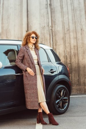 Photo for Smiling stylish ginger woman in coat and sunglasses posing near car at city street - Royalty Free Image