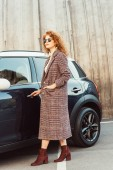 fashionable curly ginger woman in coat and sunglasses opening automobile door at city street