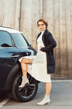 confident stylish woman in coat and eyeglasses posing and putting leg on wheel of car at urban street