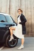 """Постер, картина, фотообои """"уверен, стильная женщина в пальто и очки позирует и положить ноги на колесе автомобиля на городской улице"""""""