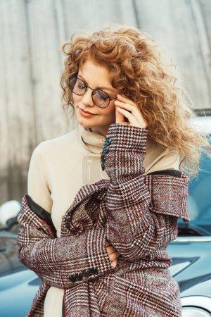 Photo pour Foyer sélectif de femme gingembre élégant réglage des lunettes près de la voiture à la rue urbaine - image libre de droit