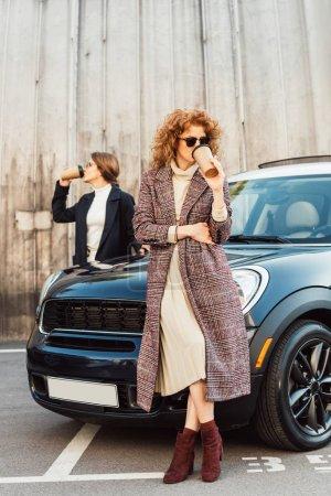 adult female models in coats drinking coffee near car at urban street