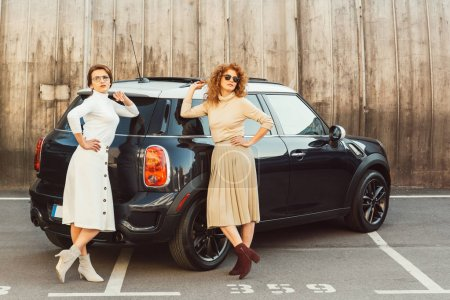 adult fashionable female models in turtle necks and skirts posing near car at street