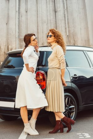 stylish adult female models in sunglasses and skirts posing near car at urban street