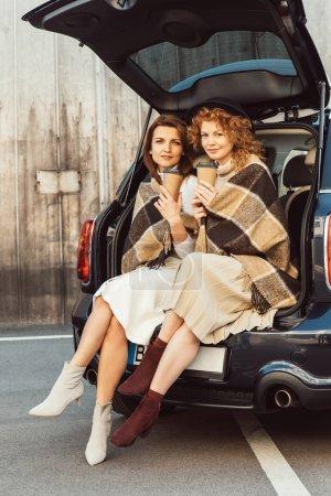 Foto de Amigas atractivas envueltas en mantas sosteniendo las tazas de café desechables y sentado en el baúl del auto en la calle de la ciudad - Imagen libre de derechos