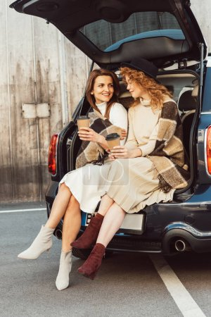 Photo for Smiling female friends holding disposable coffee cups and talking while sitting in car trunk at city street - Royalty Free Image