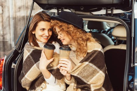 Photo for Happy adult female friends wrapped in blankets holding disposable coffee cups and sitting in car trunk at urban street - Royalty Free Image