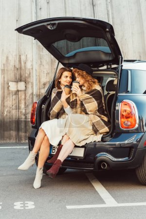 Photo for Pretty adult women wrapped in blankets holding disposable coffee cups and sitting in car trunk at city street - Royalty Free Image