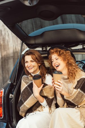 Photo for Selective focus of laughing women wrapped in blankets holding disposable coffee cups and sitting in car trunk at street - Royalty Free Image