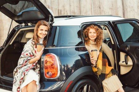 Foto de Amigas alegres envuelven en mantas sosteniendo las tazas de café desechables y sentado en el coche en la calle - Imagen libre de derechos