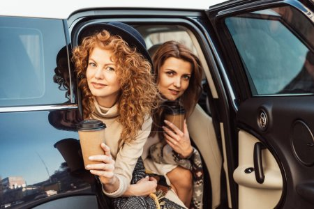pretty adult women with disposable coffee cups looking out from car at street