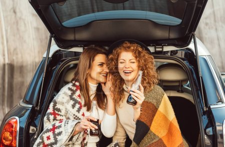 side view of smiling woman with soda bottle whispering to laughing redhead female friend in car trunk at city street